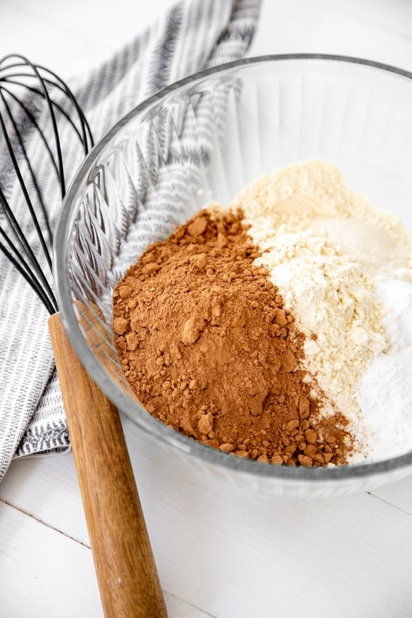 A bowl of flour, cocoa powder, and leavening with a wood whisk and a towel next to the bowl.