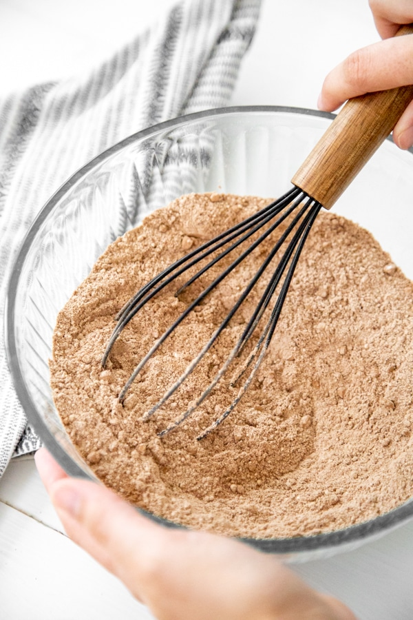 A hand whisking dry ingredients for a chocolate cake.