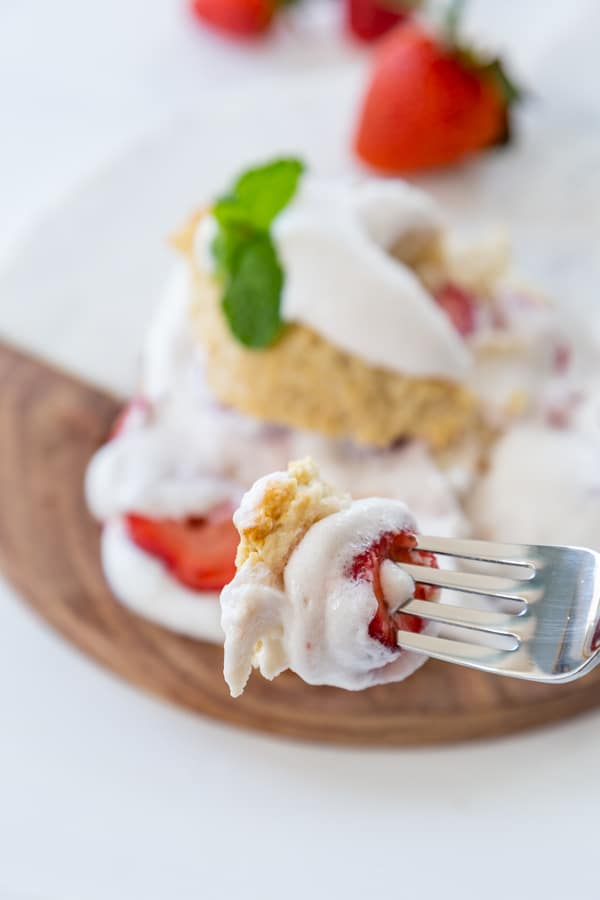 A silver fork with strawberry shortcake and a marble and wood board .