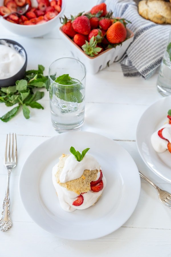 A table setting of strawberry shortcake on a white table with white plates filled with shortcakes and a container of strawberries and glasses of water with mint.