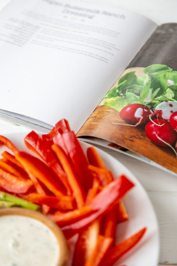 A white plate with sliced red pepper and a wood bowl with ranch dip and an open cookbook with the ranch recipe showing.