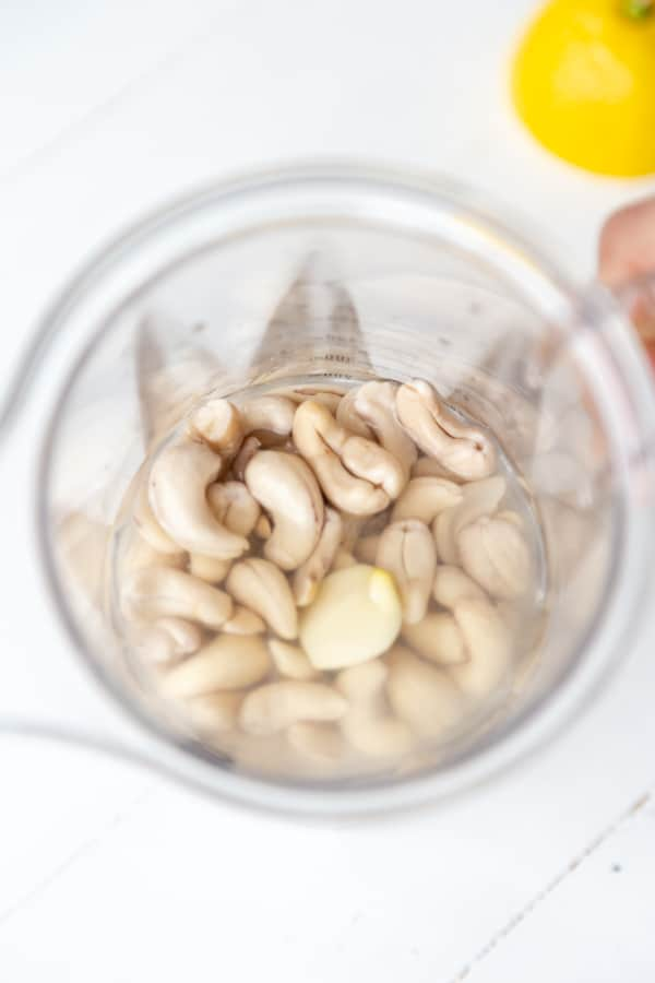 An overhead shot of cashews in a blender with a lemon on the side.
