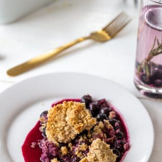 A blueberry crisp on a white plate with the pan of crisp in the background.
