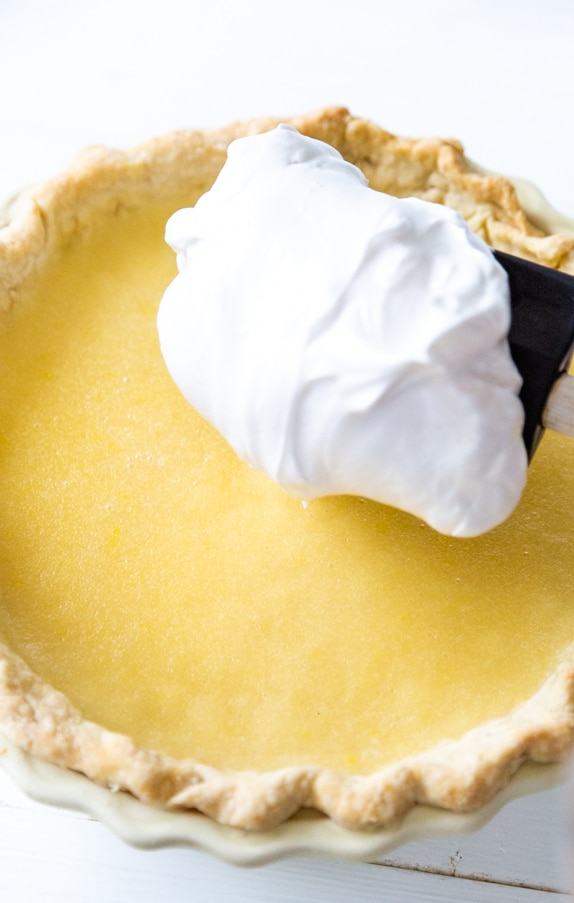 A lemon pie with a spatula of meringue being spread on top.