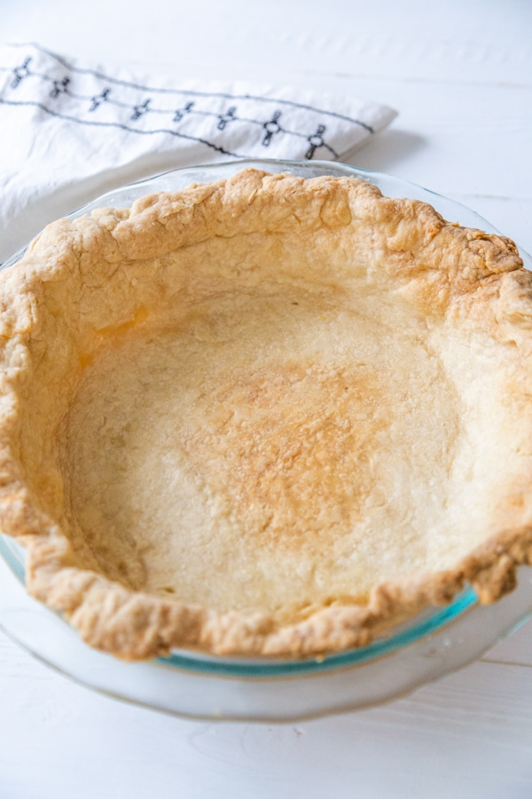 A homemade pie crust in a pie plate.
