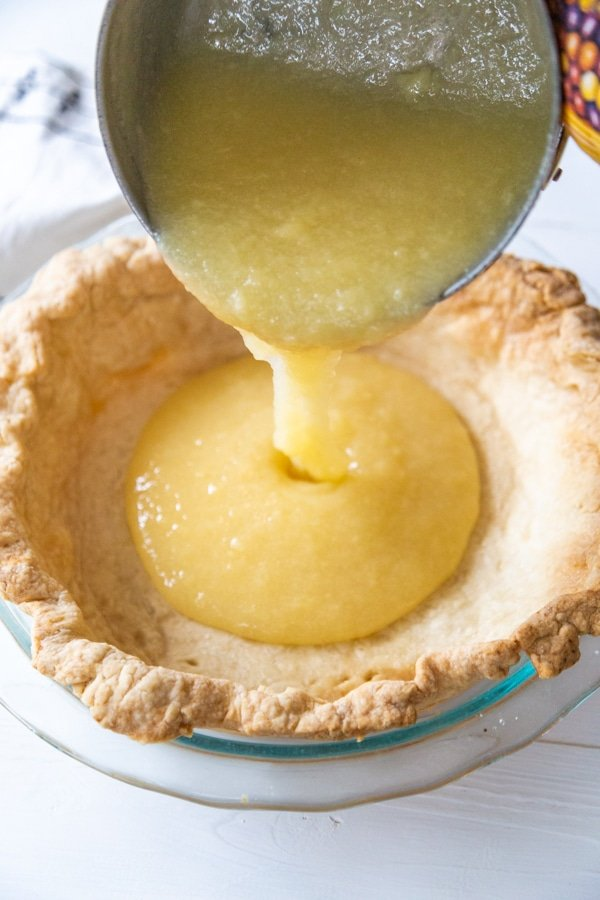 Lemon curd being poured into a pie crust.
