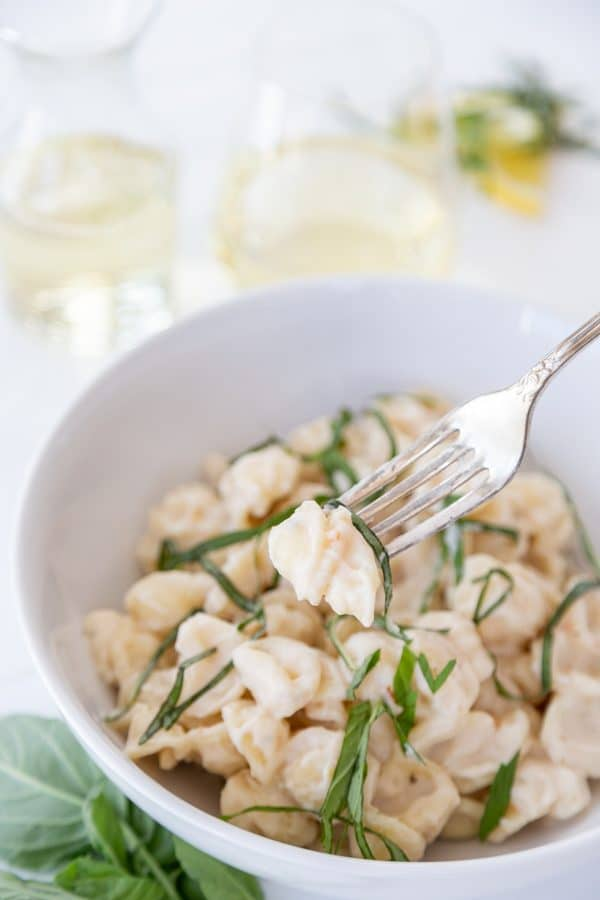 A white bowl of pasta with cream sauce and ribbons of basil with a gold fork in the bowl.