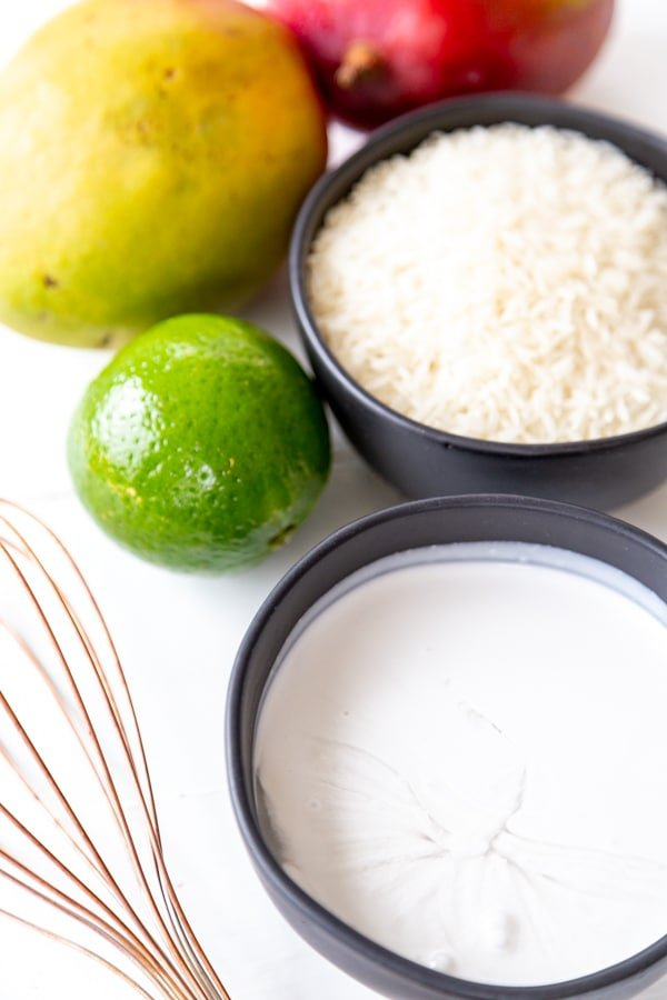 A bowl of milk, rice, a lime, mangos, and a copper whisk on a white table.