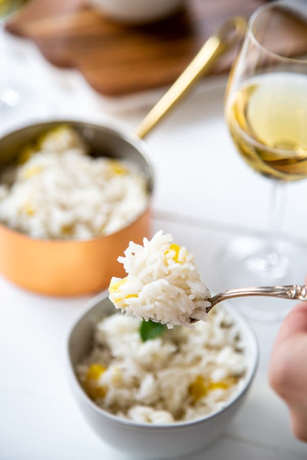 A hand holding a fork with mango rice over a bowl of rice and a copper pot of rice and a glass of wine in the background.