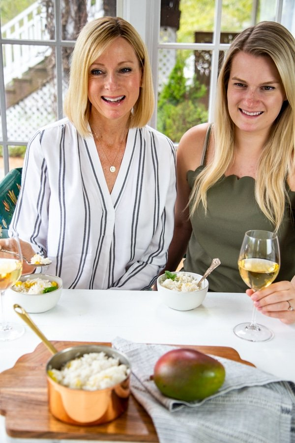 Two blonde women smiling and eating a bowl of rice and drinking white wine.
