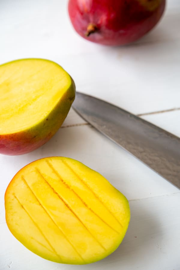 A mango cut in half with one half sliced vertically.