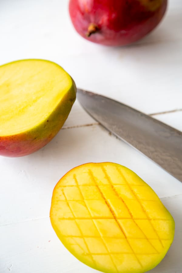 half of a sliced mango and the other half of the mango not sliced.