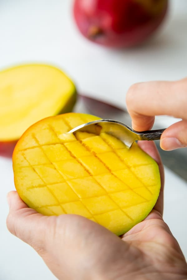A hand with a spoon scooping out sliced mango.