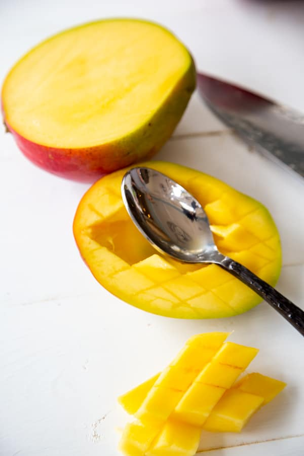 A mango cut in half with the center scooped out with a spoon.