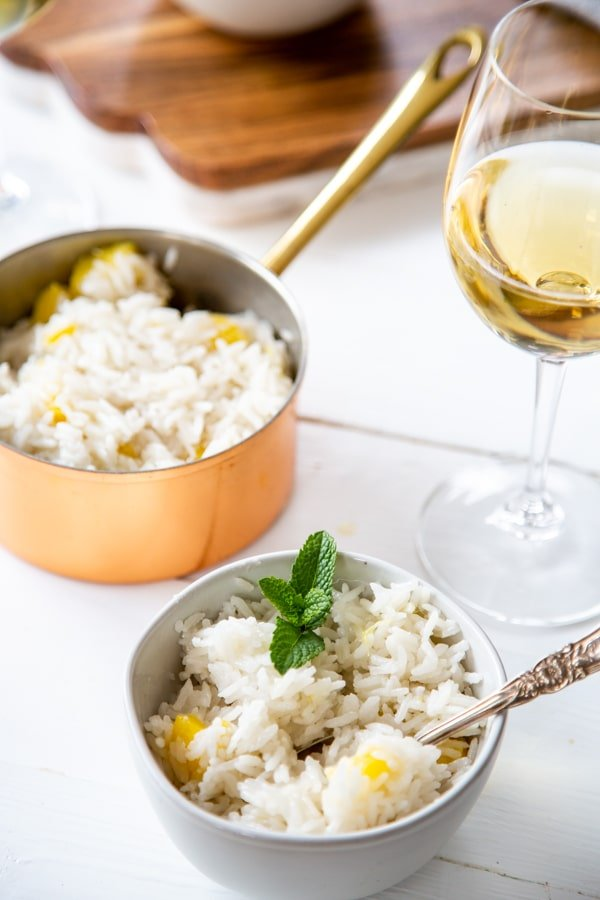 A bowl of coconut mango rice with a copper pot of rice and a glass of white wine.