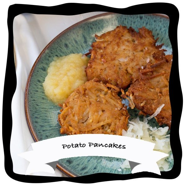 potato pancakes on a green plate with apple sauce and sour kraut