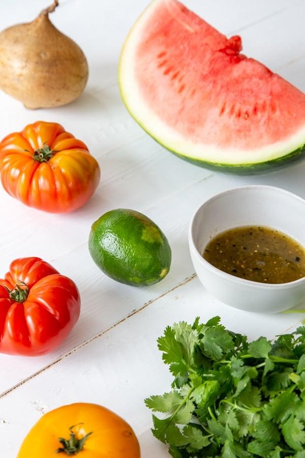 A slice of watermelon, heirloom tomatoes, a whole jicama, cilantro, and a white bowl of tomatilla salsa