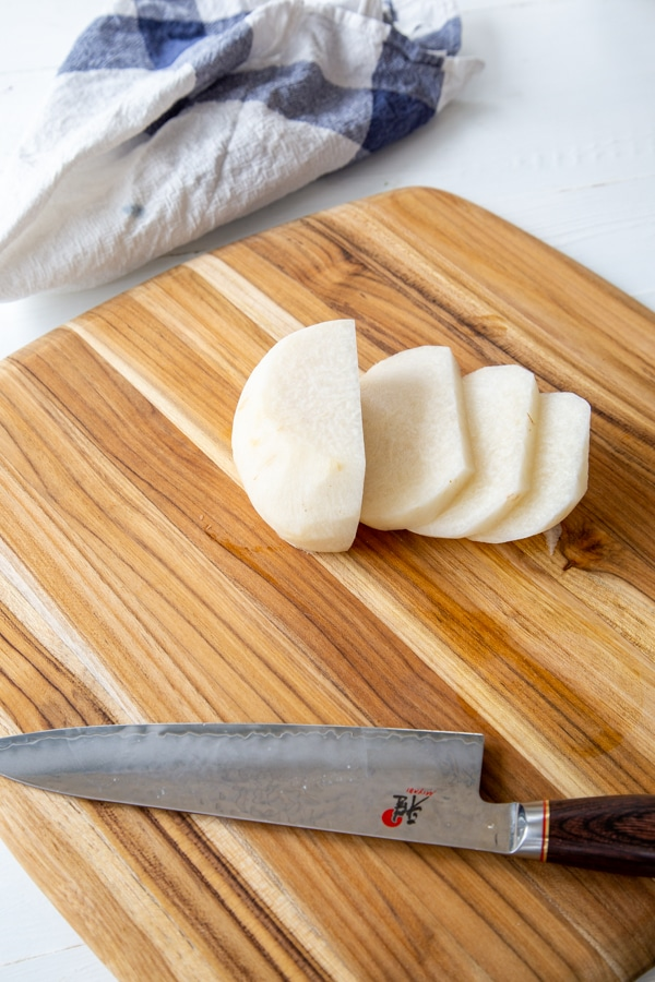 A jicama sliced into pieces on a cutting board with a knife.