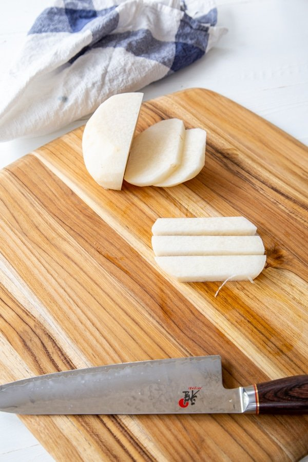A sliced jicama with one piece sliced into sticks on a wood cutting board.