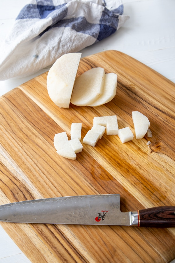 A sliced jicama with cubed pieces next to it on a wood board with a knife.