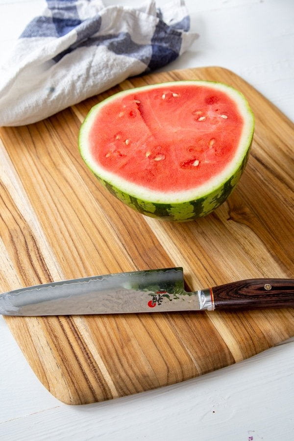 Half of a watermelon on a wood board with a knife next to it.