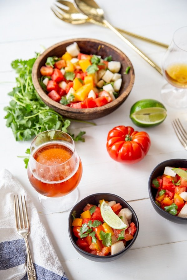 A tablescape with three bowls of salad and glasses of beer.