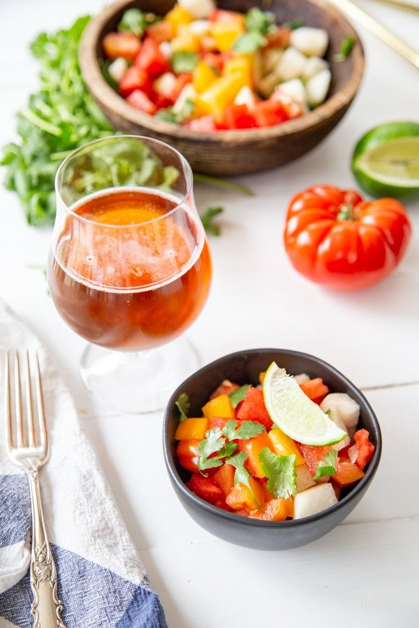 A white wood table with bowls of salad and a glass of beer.
