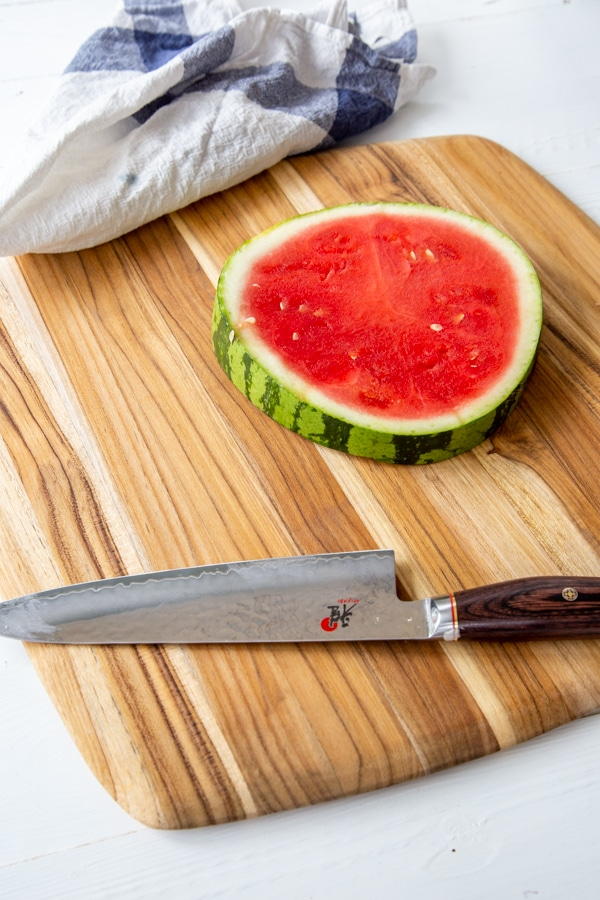 A whole slice of watermelon on a board with a knife next to it.