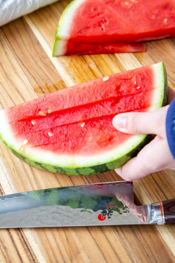 A hand holding a sliced half of watermelon.