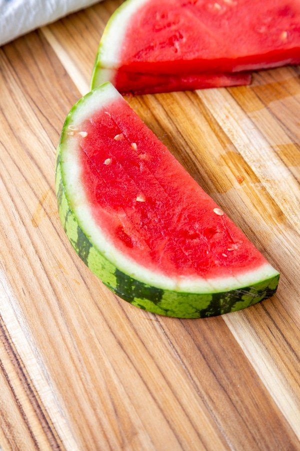 A slice of watermelon on a wood board.