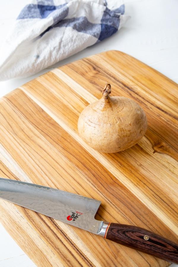 A whole unpeeled jicama on a wood board with a knife.