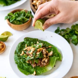 A hand squeezing a lime wedge over a vegetable lettuce wrap on a white plate with bowls of ingredients next to it.