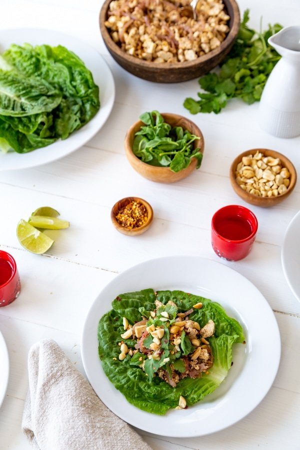 A tablescape of lettuce wraps on white plates and bowls of ingredients on a white wood table.