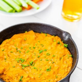An iron skillet with buffalo dip and a plate of veggie sticks and a beer behind it.