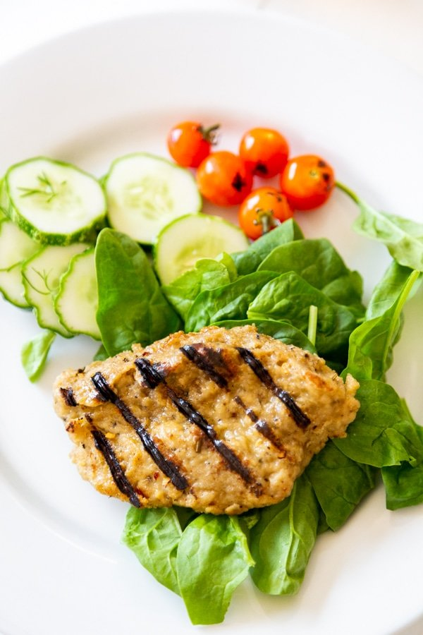 A grilled chicken breast on a bed of spinach with tomatoes and cucumbers on a white plate.