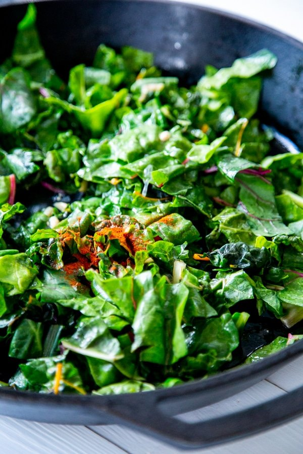 Chard in an iron skillet with red spices.