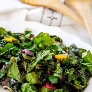 A white plate with sauteed rainbow chard and a wood serving spoon and fork in the background.