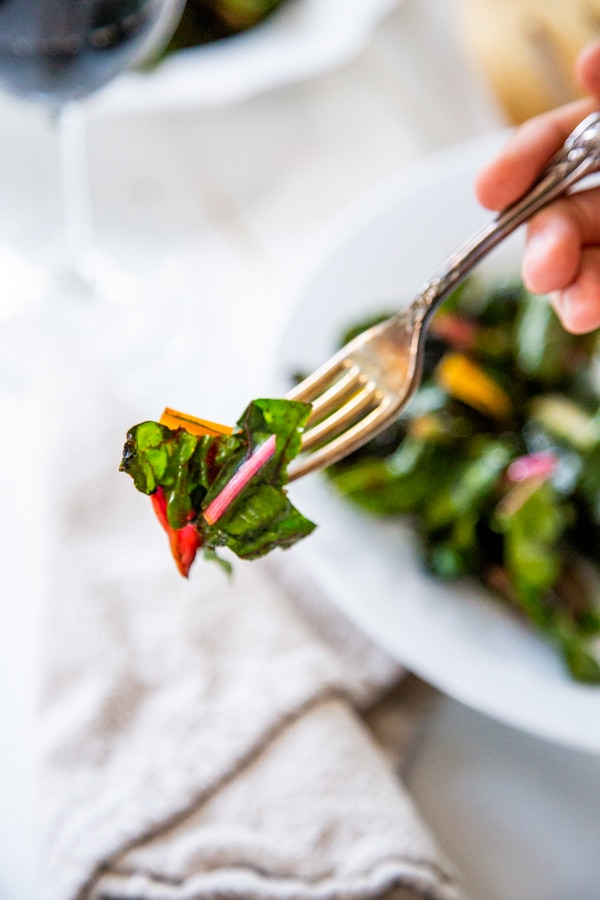A silver fork with sauteed rainbow chard held over a white plate filled with the chard.