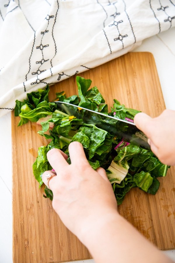 Hands chopping Swiss chard on a wood cutting board.
