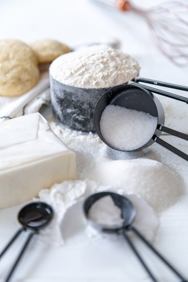The ingredients for sugar cookies in black measuring cups and spoons on a white wood board.