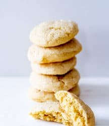 A stack of sugar cookies with on cut in half leaning on the stack.