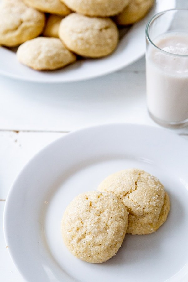 Two sugar cookies on a white plate with the platter of cookies and a glass of milk in the background.