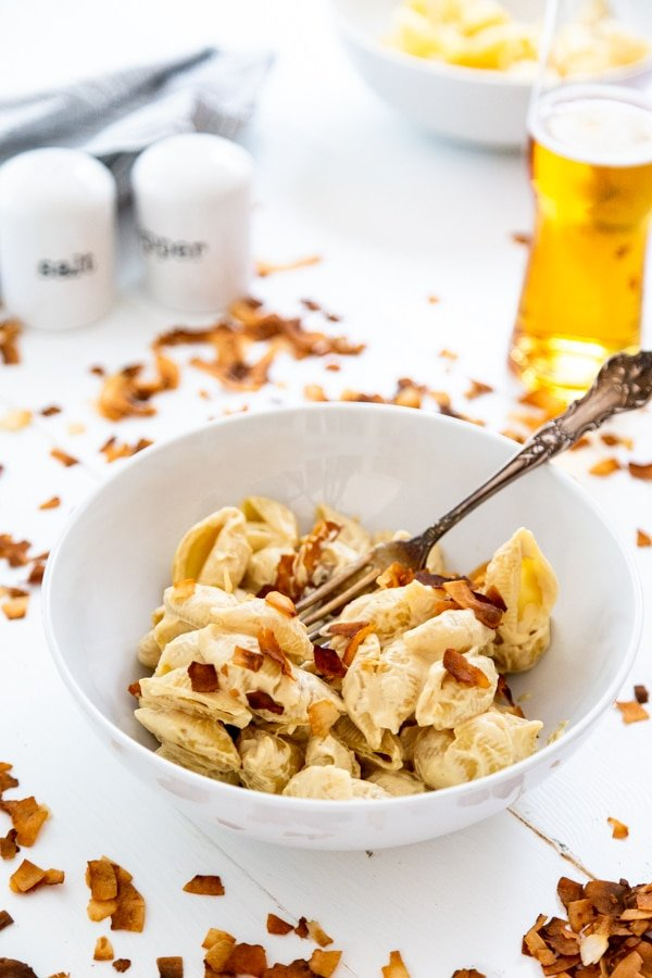A white bowl with mac and cheese sprinkled with coconut bacon in a white bowl with a silver fork in it and a beer and coconut bacon bits sprinkled next to the bowl.