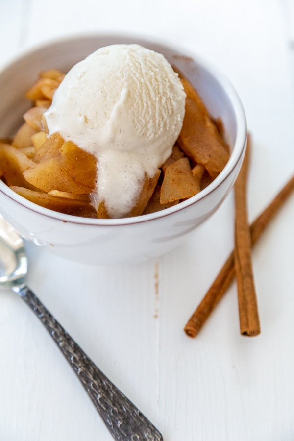 A white bowl filled with applesauce and ice cream with cinnamon sticks and a spoon next to it.