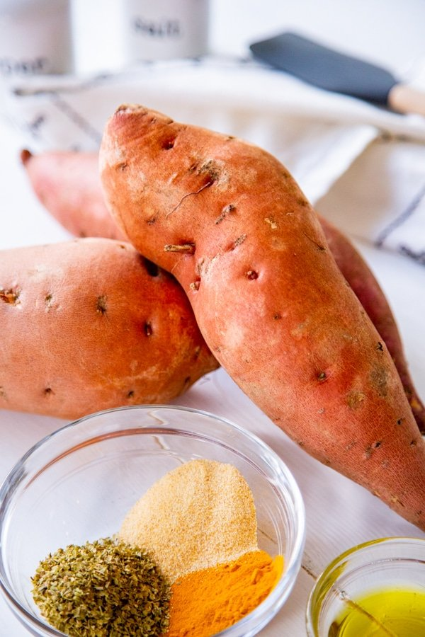 Whole sweet potatoes and a glass bowl of spices and olive oil on a white table.