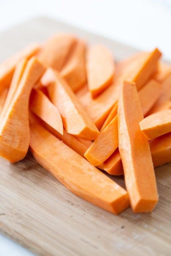 Sweet potatoes cut into fries on a wood cutting board.