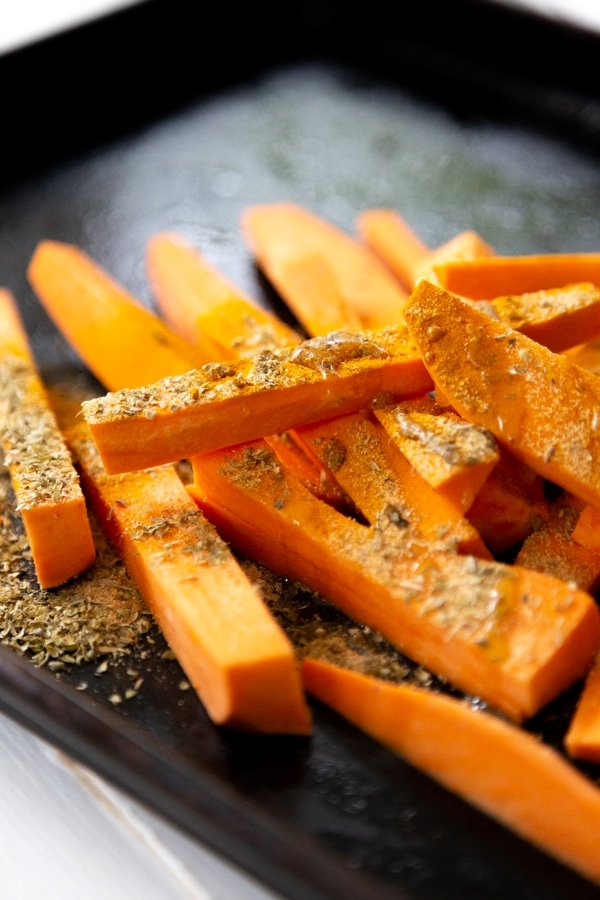 Raw sweet potato fries on a baking sheet with spices sprinkled on top.