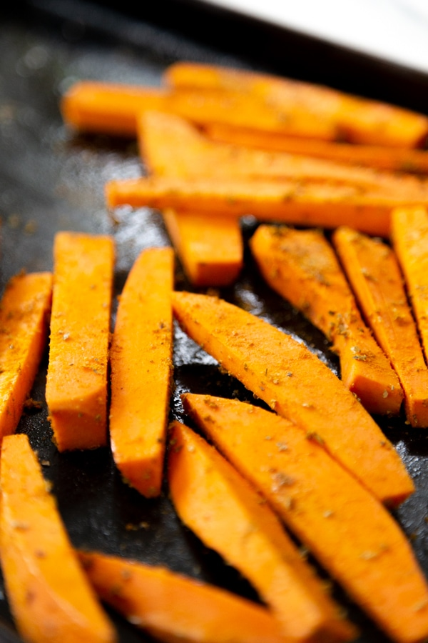 Sweet potato fries with spices on a baking sheet.