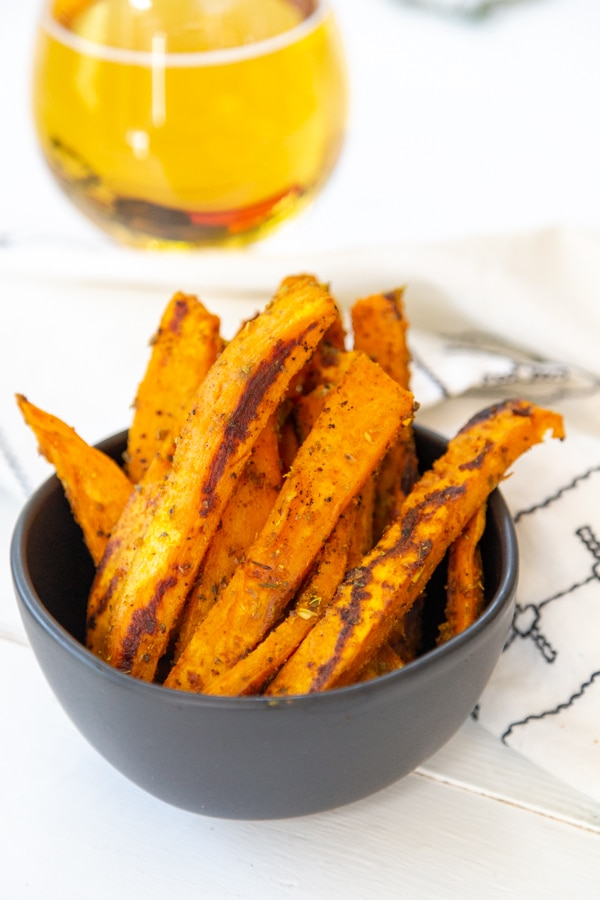 A black bowl filled with sweet potato fries and a glass of beer behind it.