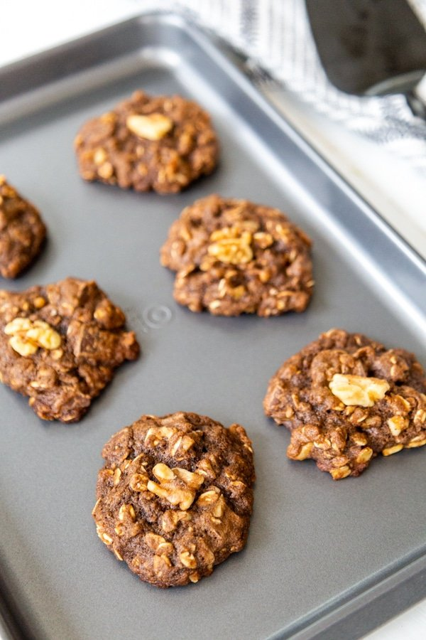 Chocolate cookies with walnuts on a baking sheet.